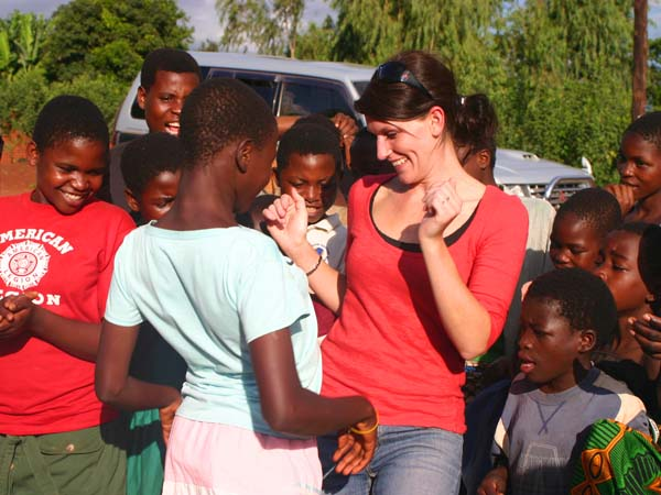 A visitor dances with kids in Malawi